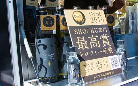 写真:だいやめの瓶とIWSC2019 SHOCHU部門最高賞トロフィー受賞の告知パネル